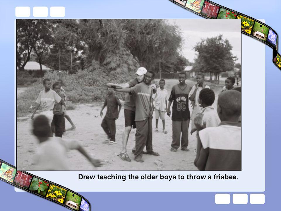Drew teaching the older boys to throw a frisbee.