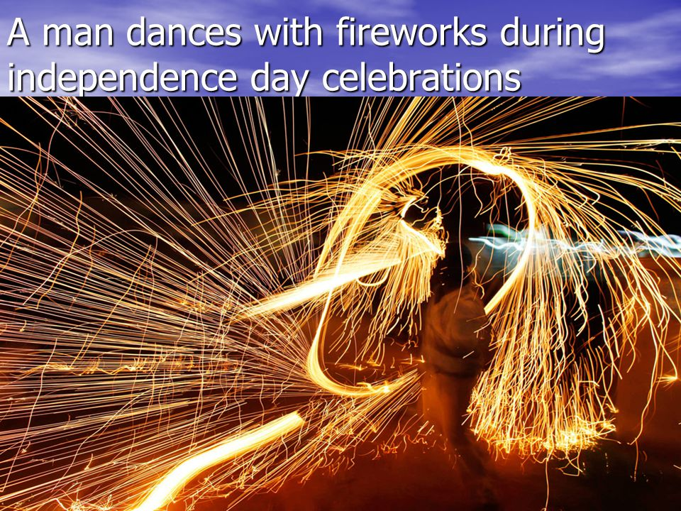 A man dances with fireworks during independence day celebrations A man dances with fireworks during independence day celebrations