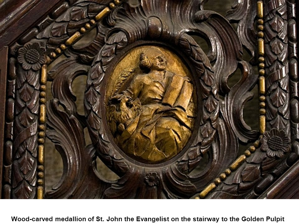 Wood-carved medallion of St. John the Evangelist on the stairway to the Golden Pulpit
