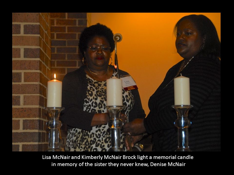 Lisa McNair and Kimberly McNair Brock light a memorial candle in memory of the sister they never knew, Denise McNair