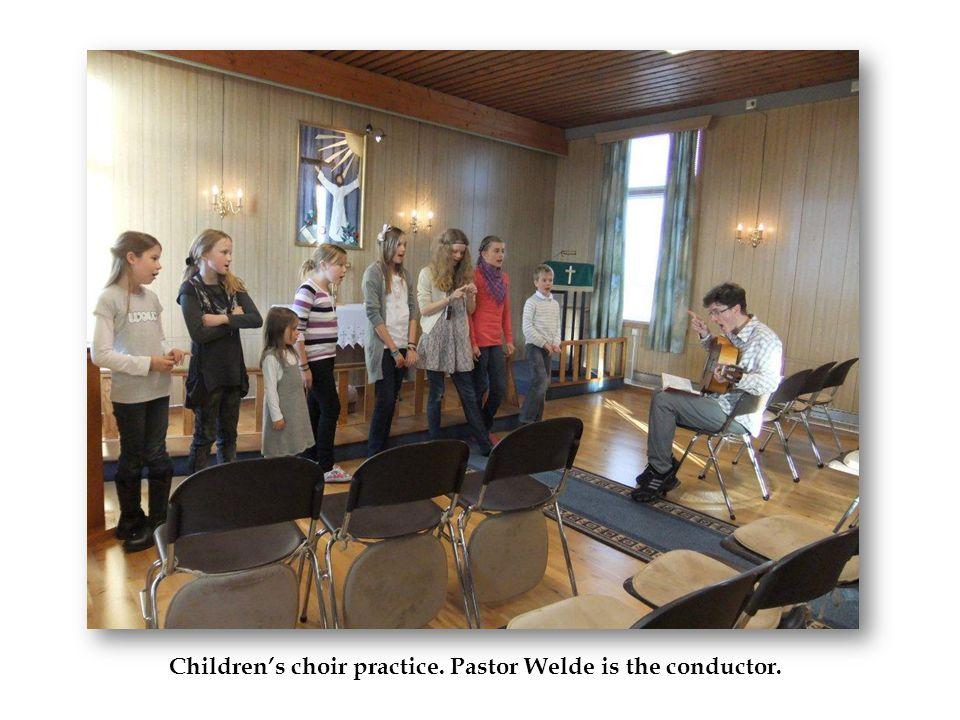 Children's choir practice. Pastor Welde is the conductor.