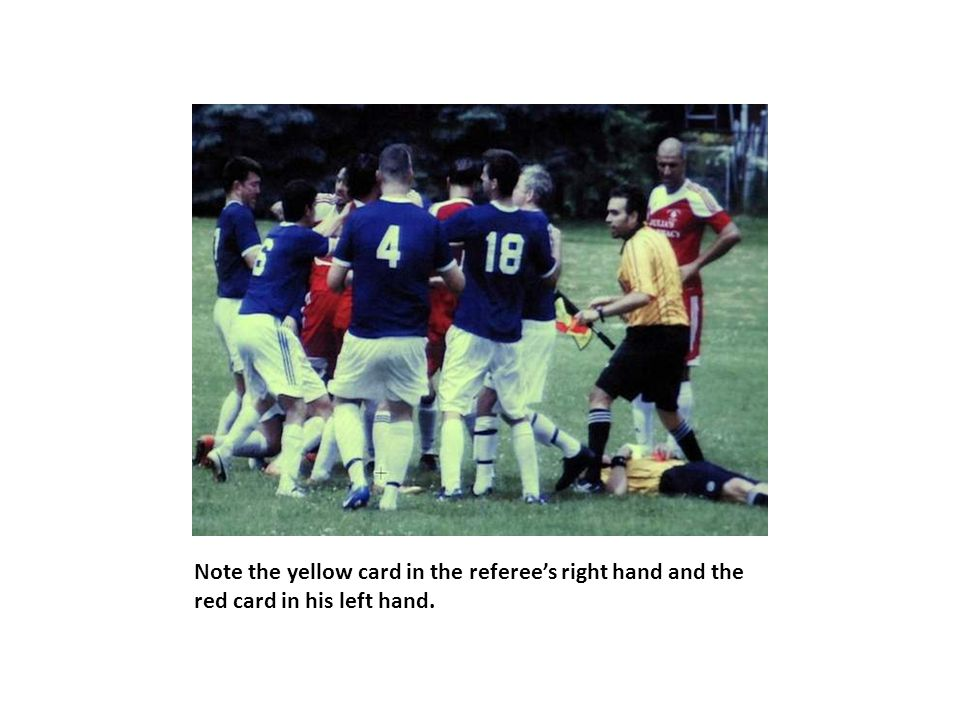 Note the yellow card in the referee's right hand and the red card in his left hand.