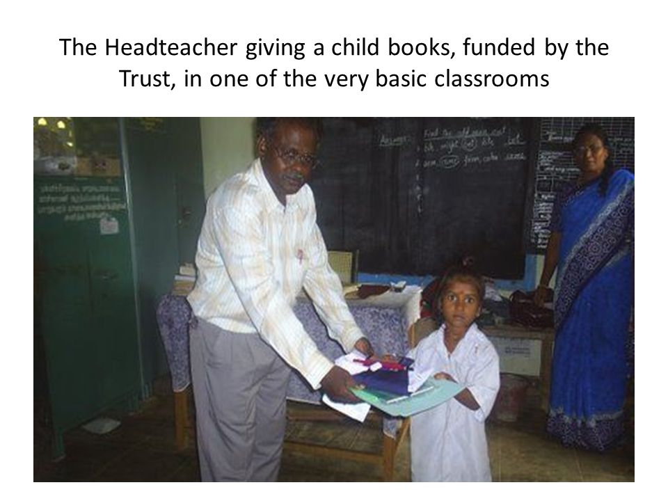The Headteacher giving a child books, funded by the Trust, in one of the very basic classrooms