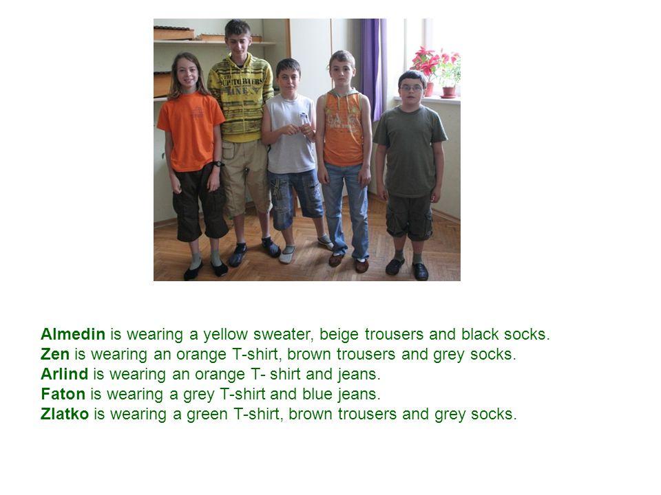 Almedin is wearing a yellow sweater, beige trousers and black socks. Zen is wearing an orange T-shirt, brown trousers and grey socks. Arlind is wearin