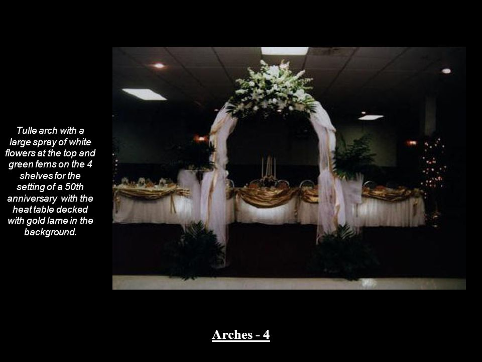 Tulle arch with a large spray of white flowers at the top and green ferns on the 4 shelves for the setting of a 50th anniversary with the heat table d
