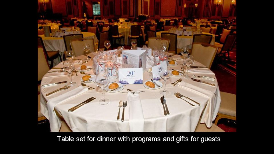 Table set for dinner with programs and gifts for guests