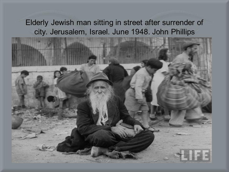 Elderly Jewish man sitting in street after surrender of city.