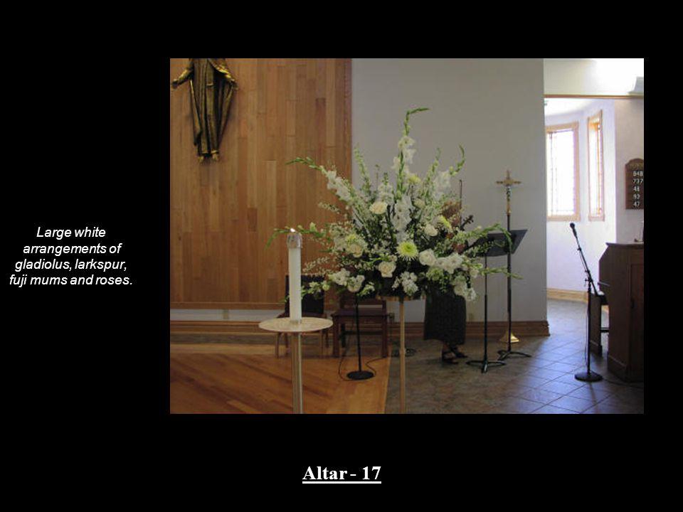 Large white arrangements of gladiolus, larkspur, fuji mums and roses. Altar - 17