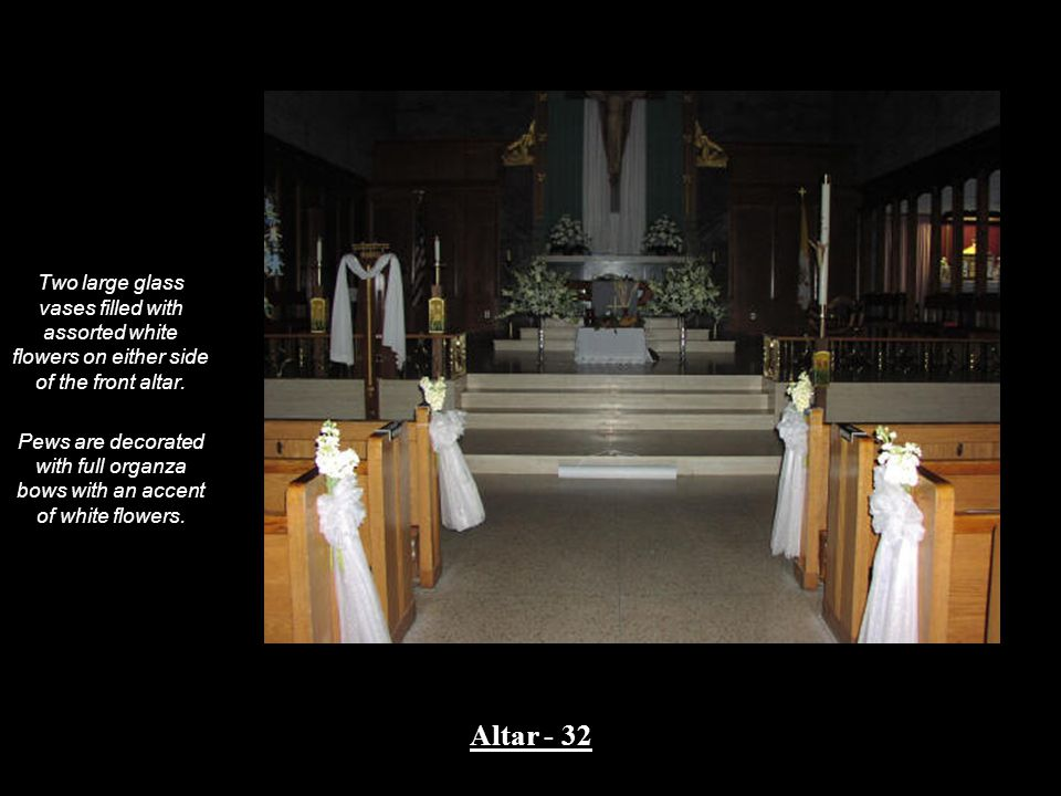 Two large glass vases filled with assorted white flowers on either side of the front altar.