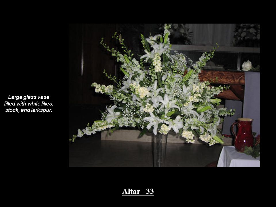 Large glass vase filled with white lilies, stock, and larkspur. Altar - 33