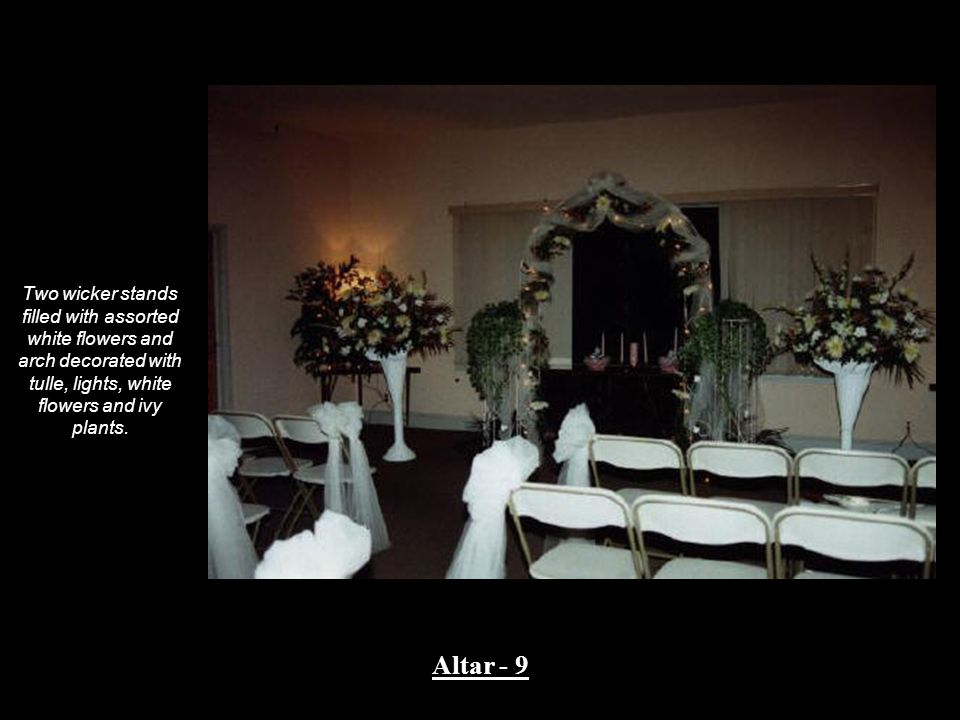 Two wicker stands filled with assorted white flowers and arch decorated with tulle, lights, white flowers and ivy plants.