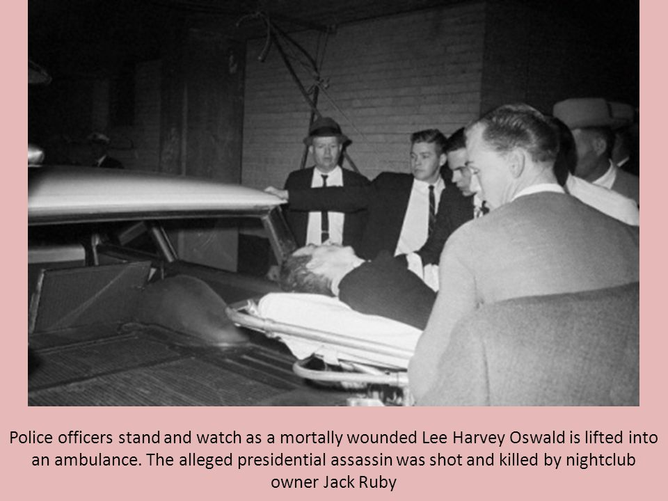 Police officers stand and watch as a mortally wounded Lee Harvey Oswald is lifted into an ambulance.