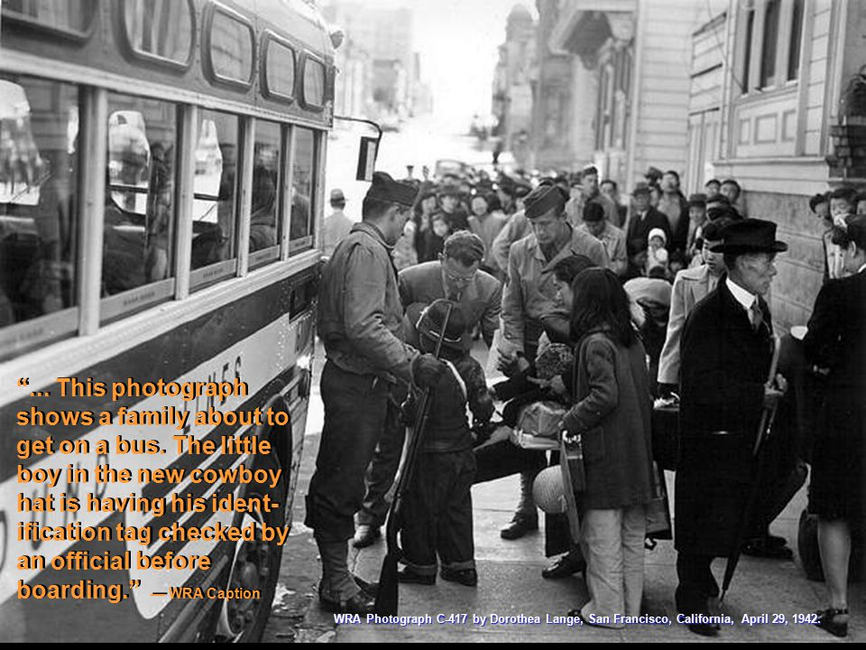 """... This photograph shows a family about to get on a bus. The little boy in the new cowboy hat is having his ident- ification tag checked by an offic"