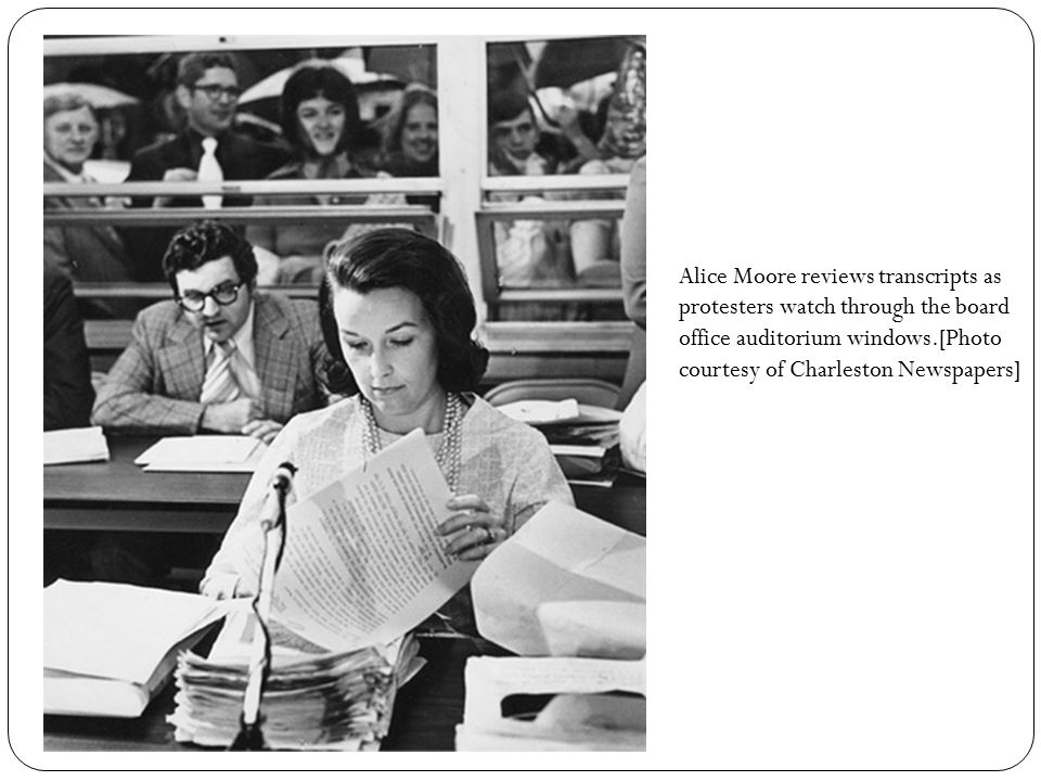 Alice Moore reviews transcripts as protesters watch through the board office auditorium windows.[Photo courtesy of Charleston Newspapers]