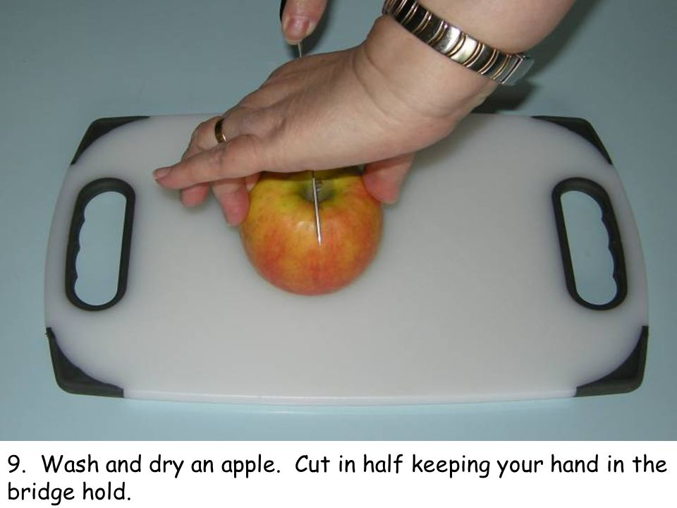9. Wash and dry an apple. Cut in half keeping your hand in the bridge hold.