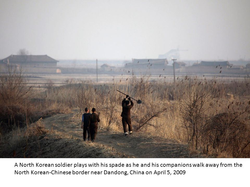 North Korean boys throw stones at a passing boat from the riverbank of the Yalu River northeast of Siniuju on April 3, 2009, across from Dandong, Chin