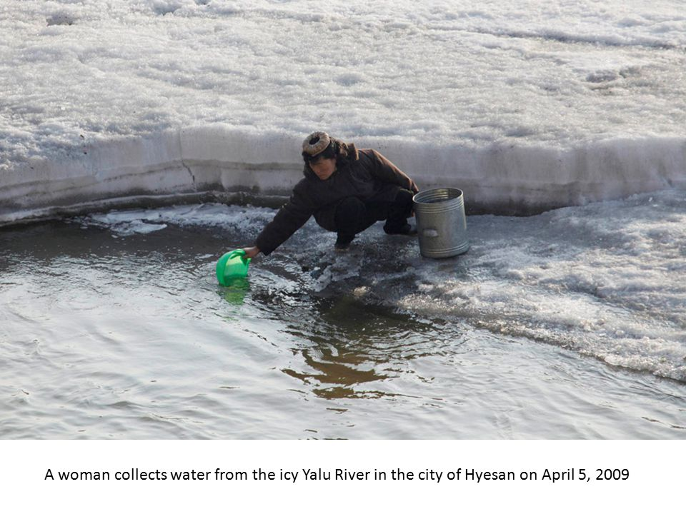 A woman carries water she collected from the Yalu River in the North Korean city of Hyesan on April 6, 2009