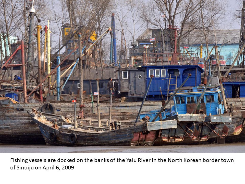 A North Korean soldier plays a guitar on the banks of the Yalu River near the town of Sinuiju, opposite the Chinese city of Dandong on April 15, 2009