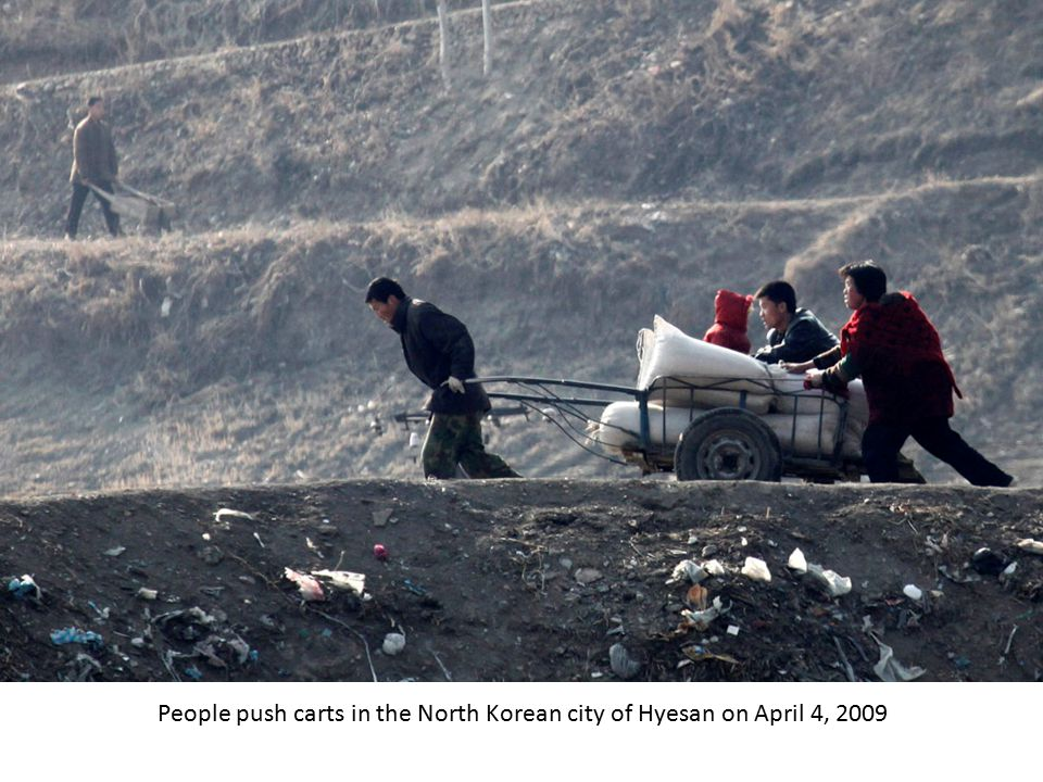 North Korean workers walk towards a factory in the city of Hyesan on April 4, 2009