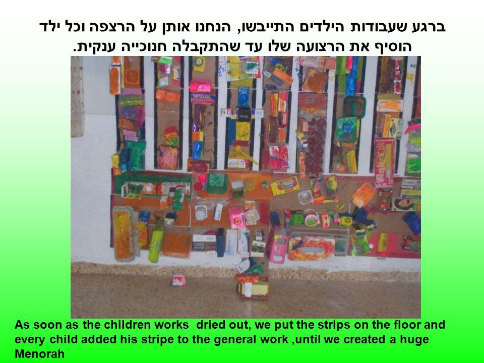 ברגע שעבודות הילדים התייבשו, הנחנו אותן על הרצפה וכל ילד הוסיף את הרצועה שלו עד שהתקבלה חנוכייה ענקית.