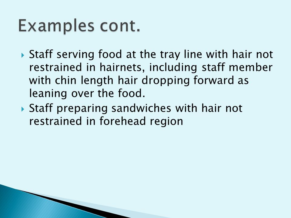  Staff serving food at the tray line with hair not restrained in hairnets, including staff member with chin length hair dropping forward as leaning over the food.