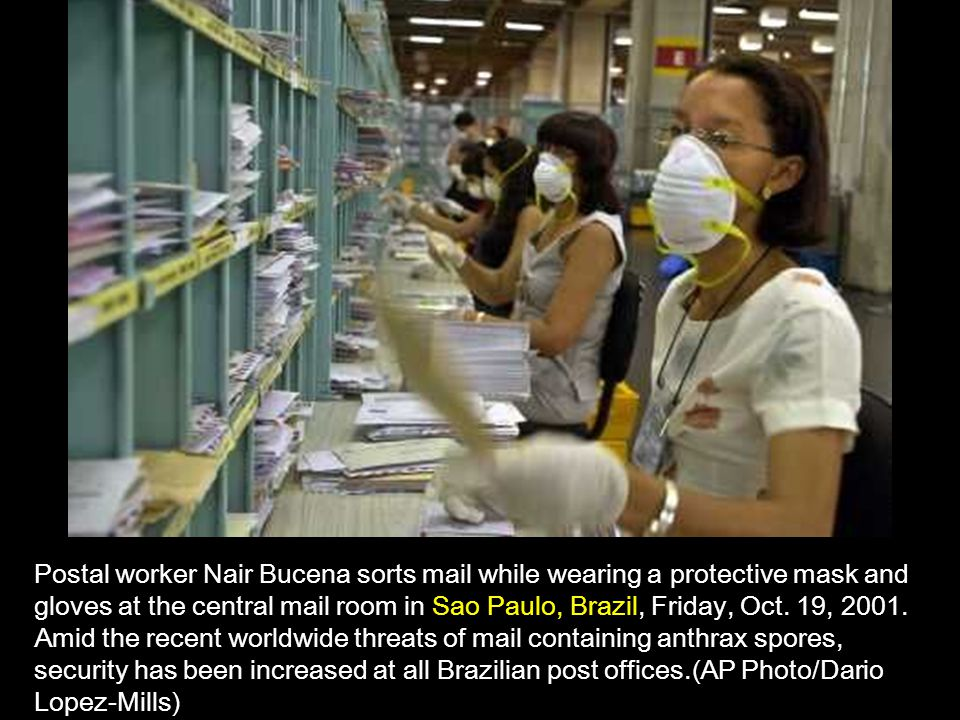 Postal worker Nair Bucena sorts mail while wearing a protective mask and gloves at the central mail room in Sao Paulo, Brazil, Friday, Oct.