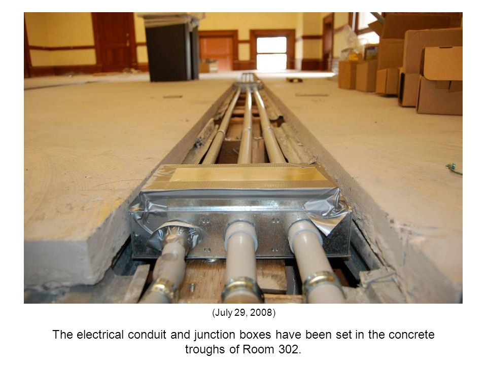The electrical conduit and junction boxes have been set in the concrete troughs of Room 302. (July 29, 2008)