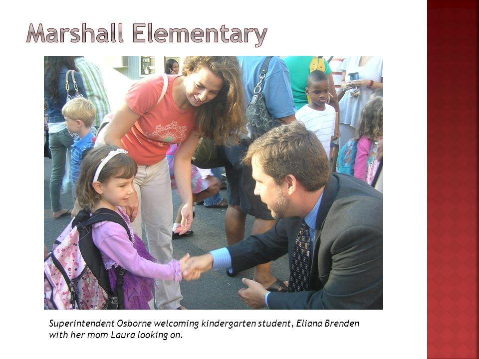 Superintendent Osborne welcoming kindergarten student, Eliana Brenden with her mom Laura looking on.