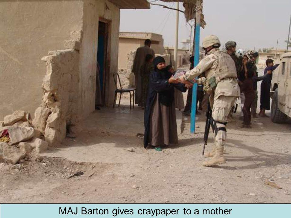 MAJ Barton gives craypaper to a mother