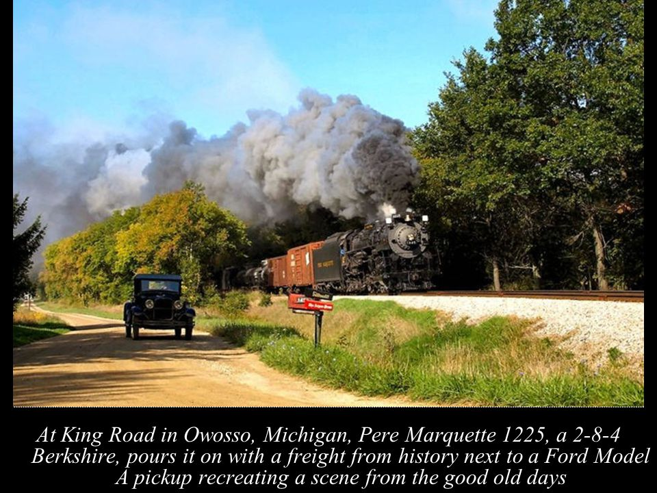 At King Road in Owosso, Michigan, Pere Marquette 1225, a 2-8-4 Berkshire, pours it on with a freight from history next to a Ford Model A pickup recreating a scene from the good old days