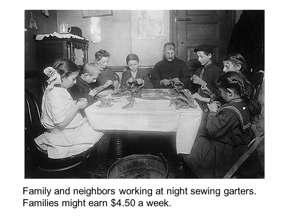 Family and neighbors working at night sewing garters. Families might earn $4.50 a week.
