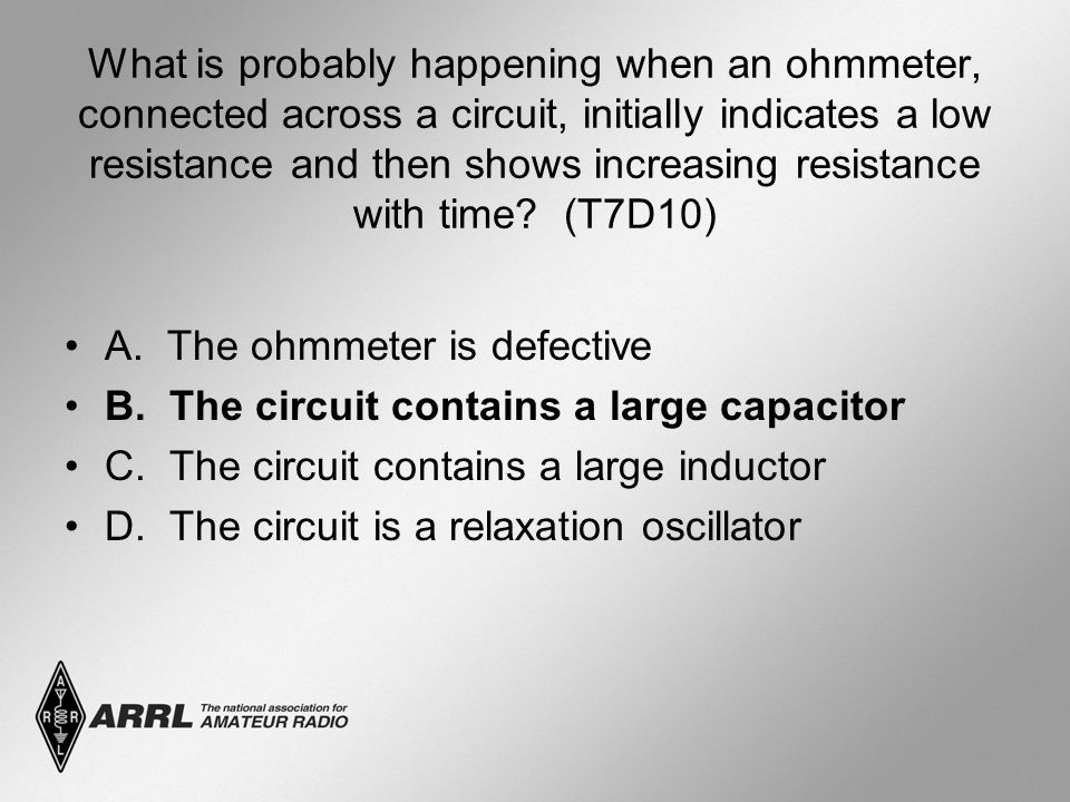 What is probably happening when an ohmmeter, connected across a circuit, initially indicates a low resistance and then shows increasing resistance with time.