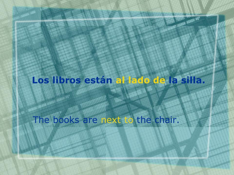 Los libros están al lado de la silla. The books are next to the chair.