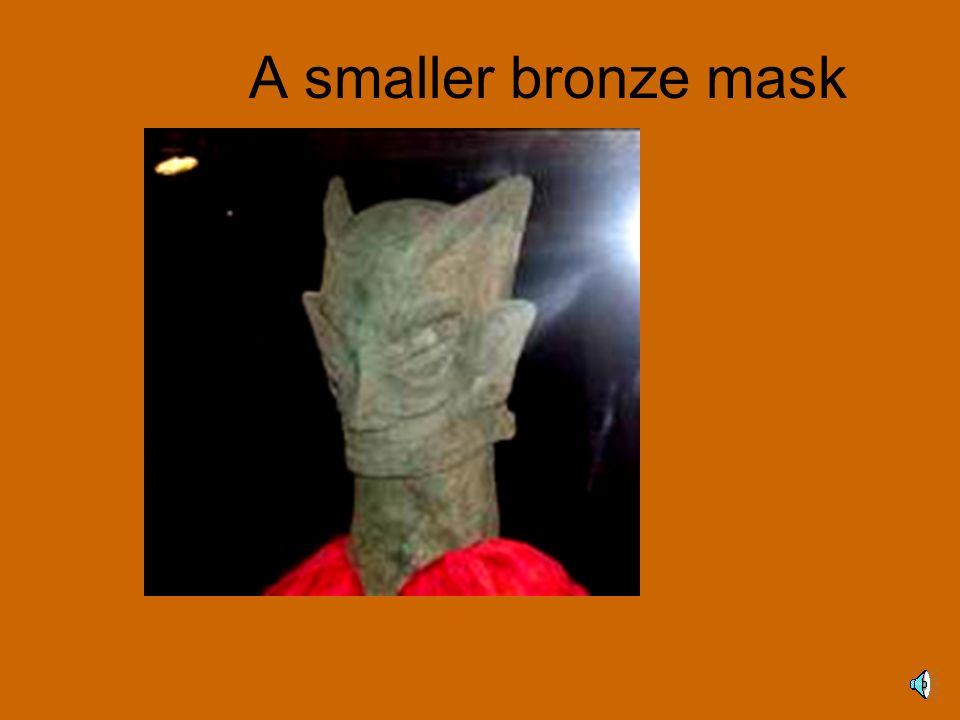 A smaller bronze mask