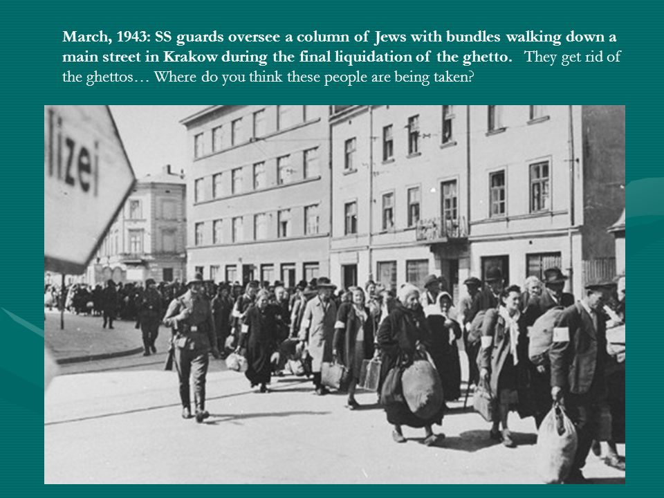 March, 1943: SS guards oversee a column of Jews with bundles walking down a main street in Krakow during the final liquidation of the ghetto. They get