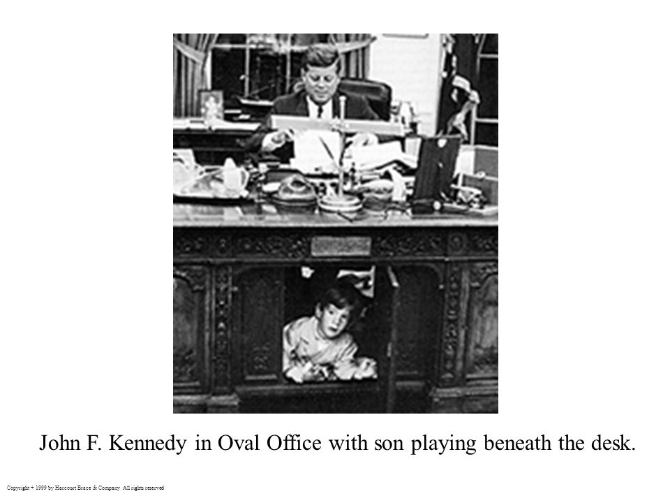John F. Kennedy in Oval Office with son playing beneath the desk.