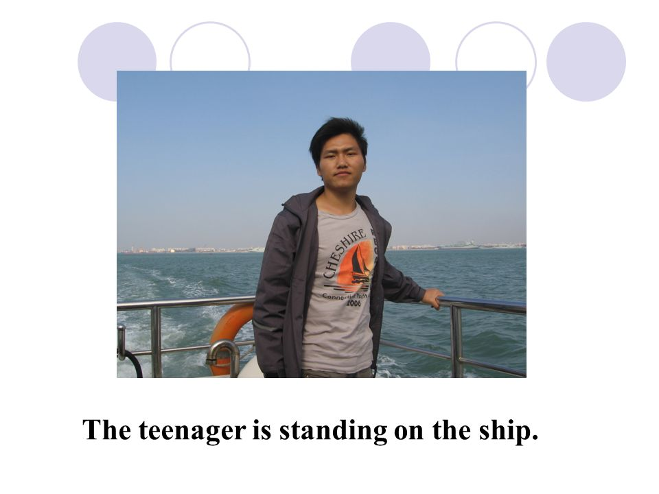 The teenager is standing on the ship.