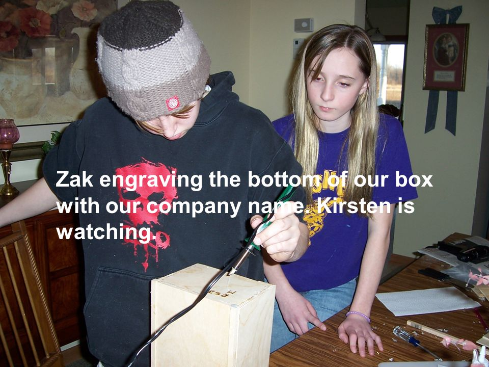 Zak engraving the bottom of our box with our company name. Kirsten is watching.