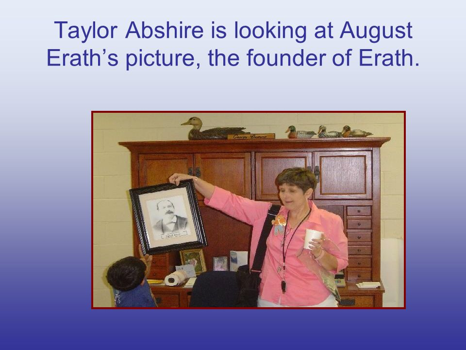 Taylor Abshire is looking at August Eraths picture, the founder of Erath.