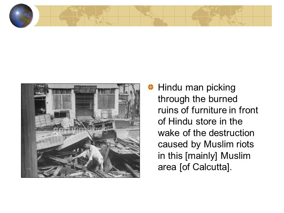 Hindu man picking through the burned ruins of furniture in front of Hindu store in the wake of the destruction caused by Muslim riots in this [mainly]
