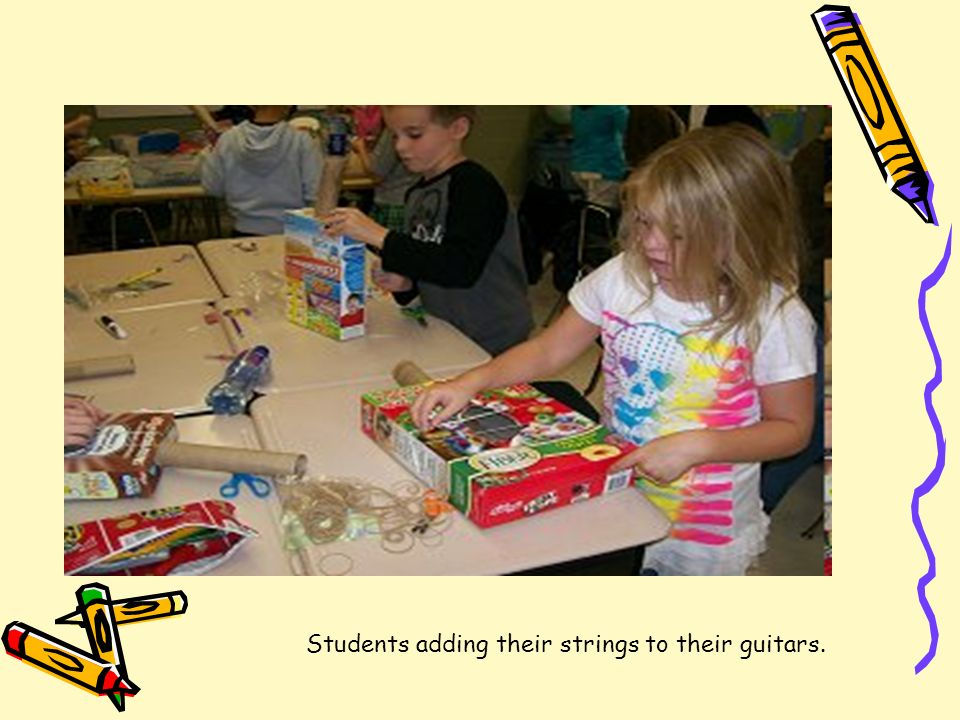 Students adding their strings to their guitars.