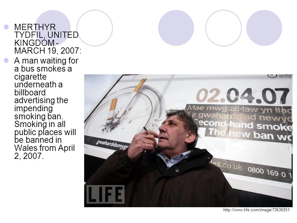 MERTHYR TYDFIL, UNITED KINGDOM - MARCH 19, 2007: A man waiting for a bus smokes a cigarette underneath a billboard advertising the impending smoking b