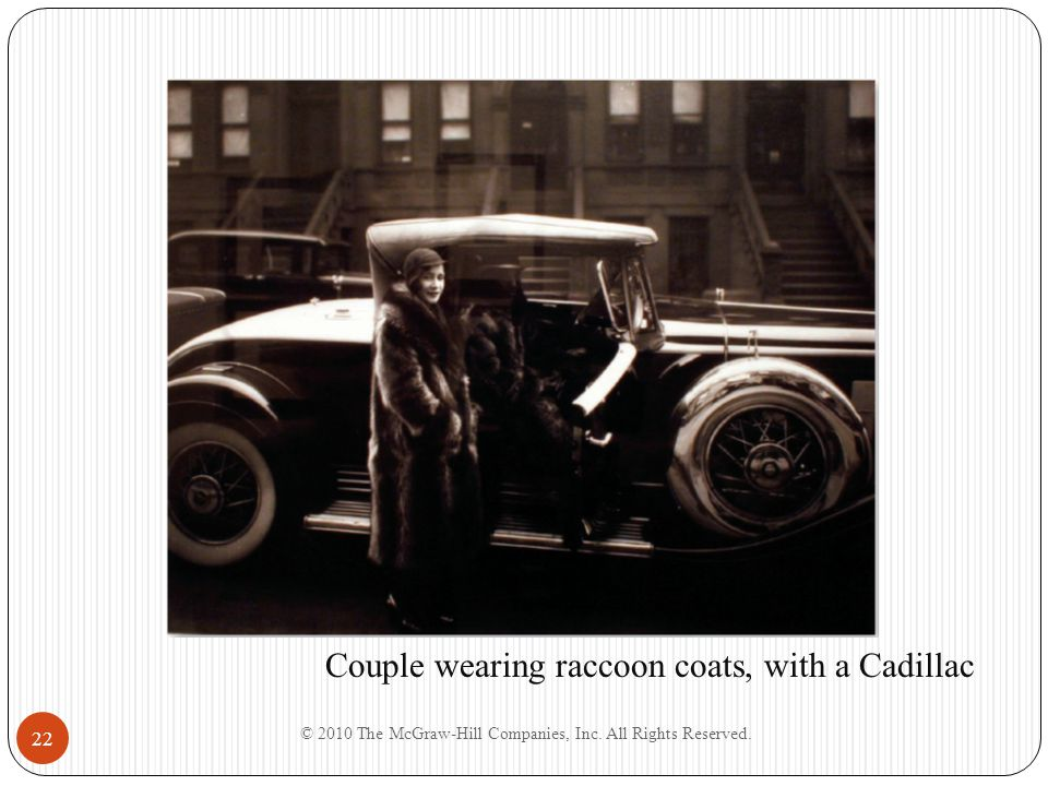 © 2010 The McGraw-Hill Companies, Inc. All Rights Reserved. 22 Couple wearing raccoon coats, with a Cadillac