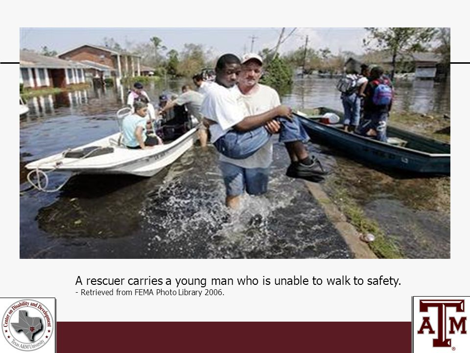 A rescuer carries a young man who is unable to walk to safety.