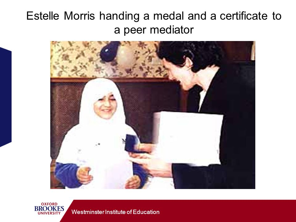 Westminster Institute of Education Estelle Morris handing a medal and a certificate to a peer mediator