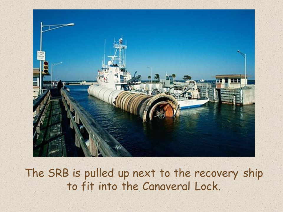 The SRB is pulled up next to the recovery ship to fit into the Canaveral Lock.