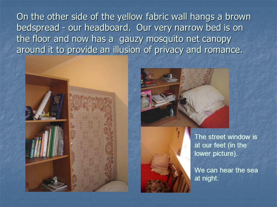 On the other side of the yellow fabric wall hangs a brown bedspread - our headboard.