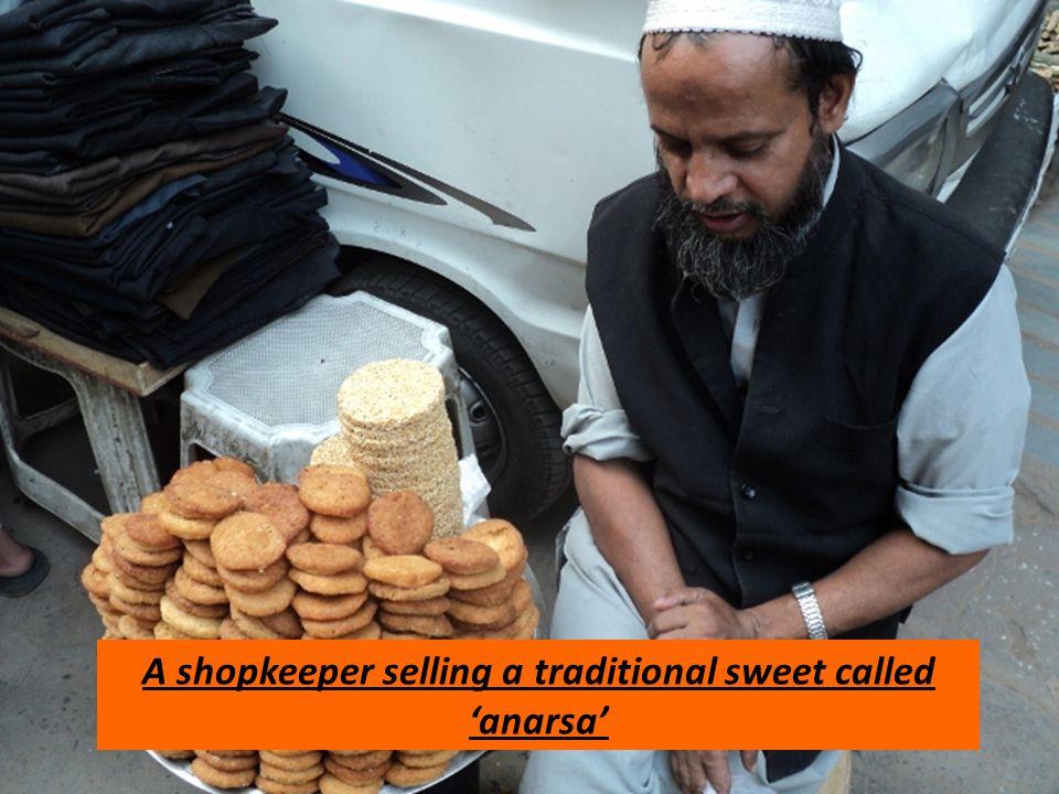 A shopkeeper selling a traditional sweet called anarsa