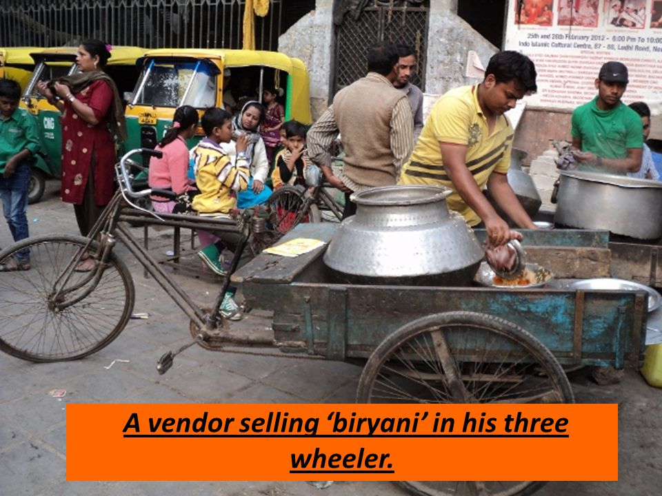 A vendor selling biryani in his three wheeler.