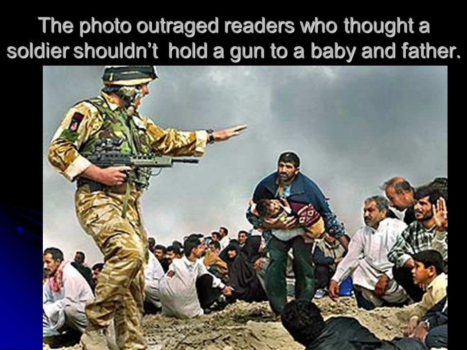 The photo outraged readers who thought a soldier shouldnt hold a gun to a baby and father.